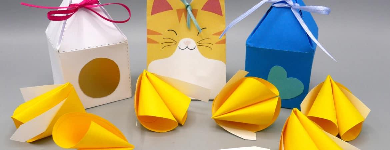 Glückskekse aus Papier mit kleinen Botschaften und dazu passende Boxen aus Papier