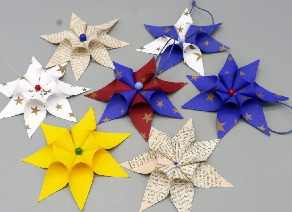 Weihnachtliche Sterne aus verschiedenen Papieren mit Holzperlen und Aufhänger