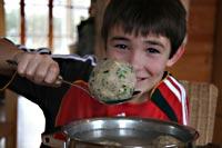 Junge hebt mit einem Löffel einen Knödel aus einem Topf beim Knödel-Kochkurs im Stadtmuseum Deggendorf