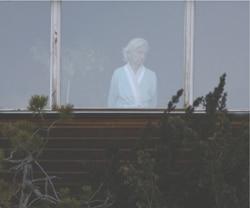 Ältere Frau steht hinter einem Fenster - Mediation im Stadtmuseum Deggendorf