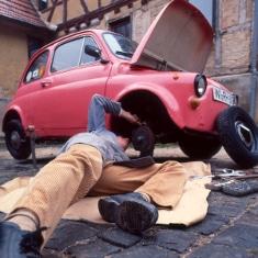 Mann liegt unter einem Fiat Oldtimer - Restaurierungsseminar Stadtmuseum Deggendorf