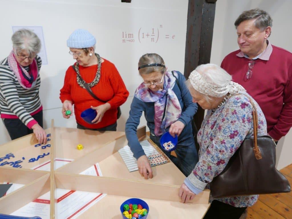 4 Seniorinnen und 1 Senior begutachten ein Ausstellungsstück der Mitmachausstellung