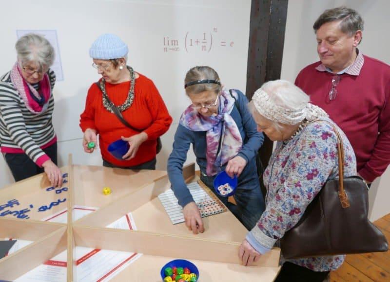 """4 Seniorinnen und 1 Senior begutachten ein Ausstellungsstück der Mitmachausstellung """"Mathematik zum Anfassen"""" im Stadtmuseum Deggendorf"""